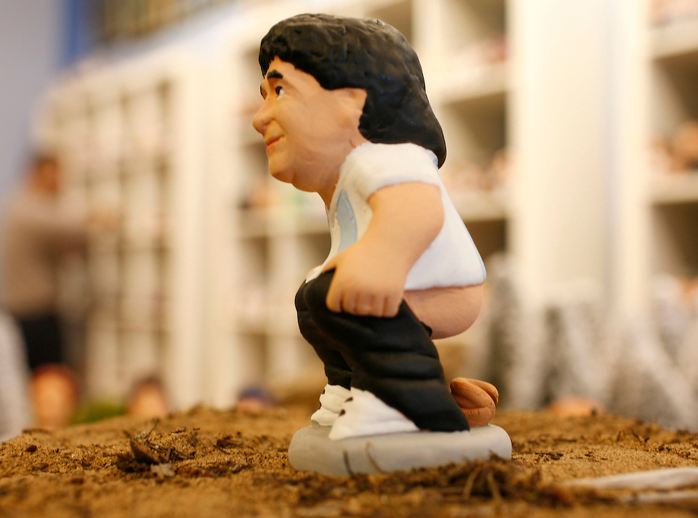 "Torroella de Mongri, Spain, 19 November 2009. .A company in Torroella de Montgrí (Girona, Spain) called ""caganer.com"" specialized in the production of ""caganers"" unveiled today  the new figures for Christmas as Argentina coach, Diego Armando Maradona. .A ""Caganer"" is a small figure from Catalonia, usually made of fired clay,  and depicted as squating person in the act defecating. .""Caganer"" is Catalan for pooper. It fomrs part of one of the typical figures of  the manger or ""Nativity"" scene together with Mary, .Joseph and the baby Jesus but hidden in a corner. It is a humorous figure, originally portraying a peasant wearing a .barretina (a red stocking hat), and seems to date from the 18th century when it  was believed that the figure's depositions  .would fertilize the earth to bring a properous year. With  the course of the time, the original  personage of this pooping figure .was  substituted with personalities from the political and sports world and other famous personalities."
