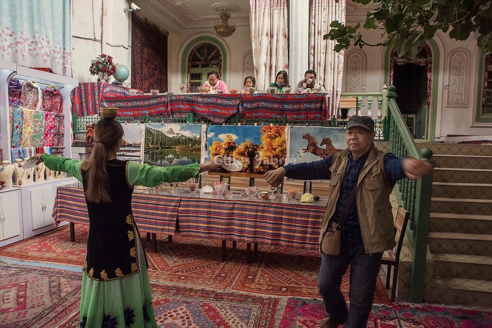 Kashgar. October 2nd, 2017<br /> A han tourist dancing a long with a Uyghur woman at a souvenir shop of Kashgar old city.