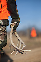 HUNTER HOLDING A SET OF RATTLING ANTLERS WHILE ANOTHER HUNTER STANDS IN THE BACKGROUND