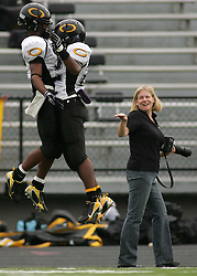 A fan celebrates along with DeSean Hales (left) and Ossam Cook after Cook's touchdown during the Panthers' 59-42 playoff victory over College Park, Saturday, November 17, 2007 at Moorehead Stadium in Conroe, TX.