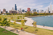 Two bicyclers ride thru Museum Campus along Lake Michigan on an Autumn day in Chicago Illinios.