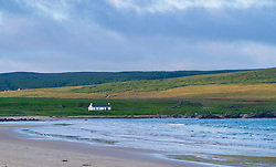 View of white cottage and sea at Laggan Bay on Islay in Inner Hebrides , Scotland, Uk