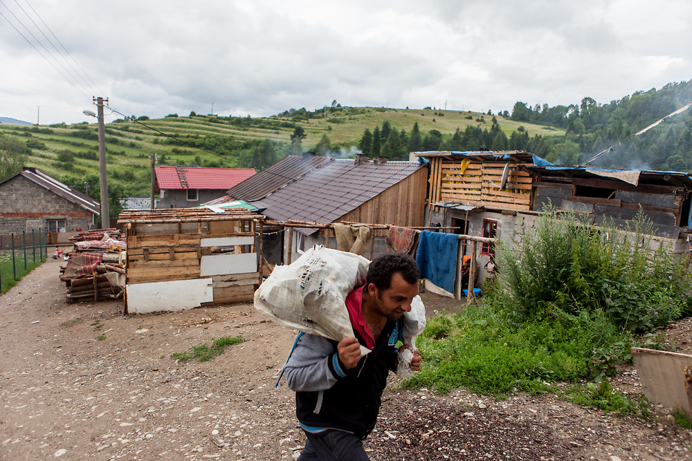 """A resident is carrying goods at the Roma part of the district """"Podsadek"""" in eastern Slovakia. The town of Stara Lubovna has a population of 16350, of whom 2 060 (13%) are of Roma origin. The majority of Roma live in the Podsadek district, where 980 (74%) out of 1330 inhabitants are Roma."""