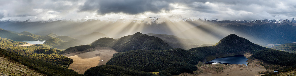 God rays form over native forest and numerous small lakes near the Borland Road in Fiordland.