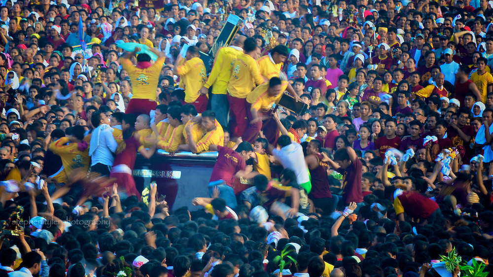 Devotees close to the carriage holding the cross and statue of the Black Nazarene swarm in the path of the procession in attempt to touch it with their personal items or pieces of cloth to gain the promise of favorable miracles.