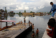During a strike in Kashmir in June, schools were closed, and young boys escaped the heat by diving off one of the main docks on Dal Lake. A Shikara owner sits idle in his boat, tied at a dock normally packed with boats and tourists.