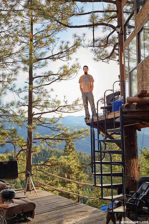 A young man proudly stands next to his handmade treehouse constructed entirely out of reclaimed materials near Wenatchee, Washington.
