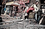 Woman passing through abandoned shopping catrs outside Chinese shops, Tronto, Canada