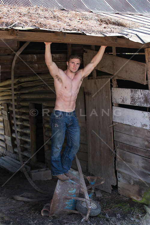 hot shirtless man standing on a rustic wheelbarrow in a barn