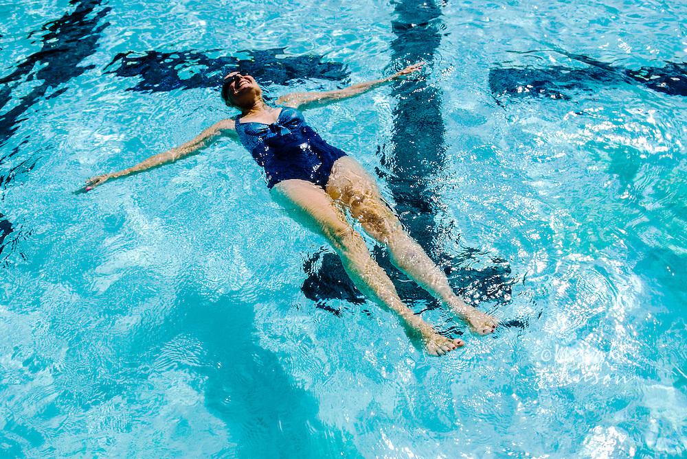 Kailua, Oahu, Hawaii, USA --- Woman Floating in Pool