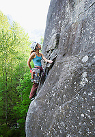 A mid-30s Caucasian woman searches for the next hold on her ascent up a rock face on Mount Index, Washington.  ..Model Release:  20080524_MR_A