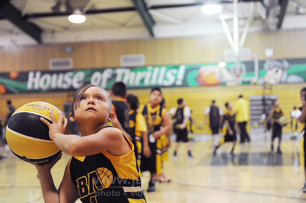 "A young player uses a full-size ball and a regulation hoop during Gil Basketball Academy's last practice for 2014 at Alisal High School in Salinas. Gil Basketball Academy's mission is to ""support the youth of Salinas as they 'Shoot for and Reach' their positive goals, by participating in organized basketball camps, clinics, college tours, motivational speaker forums, field trips and trips beyond Salinas."""