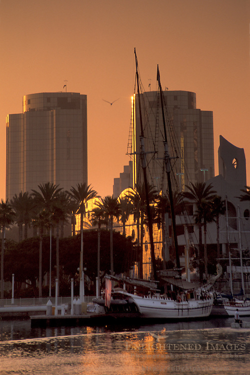 Sailing ship docked below city high rise office buildings in downtown at sunset, Long Beach Harbor, California