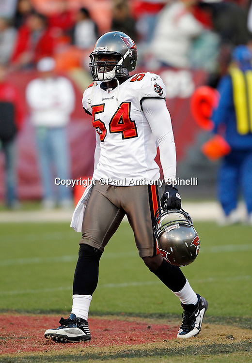 Tampa Bay Buccaneers linebacker Geno Hayes (54) smiles as he holds the helmet of a teammate during the NFL week 11 football game against the San Francisco 49ers on Sunday, November 21, 2010 in San Francisco, California. The Bucs won the game 21-0. (©Paul Anthony Spinelli)