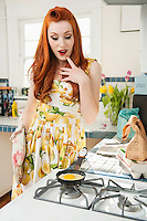 Beautiful young woman looking at omelet in frying pan