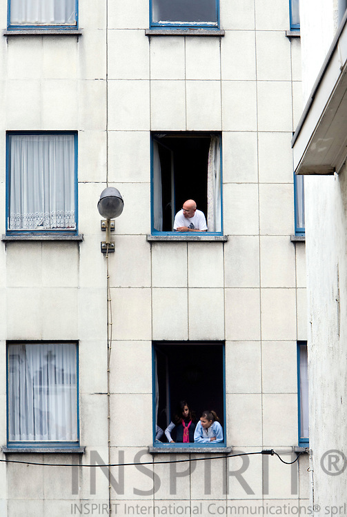 BRUSSELS - BELGIUM - 14 OCTOBER 2008 -- 2 girls in one apartment window looks out and on the upper floor a man does the same in an apartment building at Marollen, an ancient district of Brussels. Photo: Erik Luntang