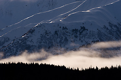 Fog lifts from the Chilkat River valley near the Takhin Ridge mountains (background). The photo was taken from the Alaska Chilkat Bald Eagle Preserve near Haines, Alaska. Mountains in the Haines area are a popular destination for heli-skiing.