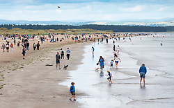 View along busy West Beach at St Andrews in summer, Scotland, UK