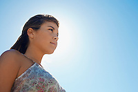 Young woman against clear blue sky close-up