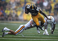 September 3, 2011: Iowa Hawkeyes running back Mika'il McCall (25) is tripped up by Tennessee Tech Golden Eagles cornerback Caleb Mitchell (15) during the first half of the game between the Tennessee Tech Golden Eagles and the Iowa Hawkeyes at Kinnick Stadium in Iowa City, Iowa on Saturday, September 3, 2011. Iowa defeated Tennessee Tech 34-7 in a game stopped at one point due to lightning and rain.