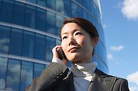 Businesswoman standing outside office building Using Cell Phone close-up