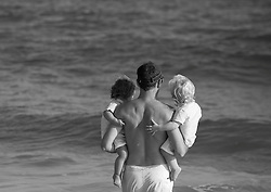 man and two young children looking at the ocean