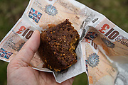 Yorkshire Parkin in fake 10 pound napkin. Hike along the River Swale from Reeth to Marske, in Yorkshire Dales National Park, England, United Kingdom, Europe. England Coast to Coast hike day 9 of 14. Overnight at Kings Head Hotel in Richmond, North Yorkshire county. [This image, commissioned by Wilderness Travel, is not available to any other agency providing group travel in the UK, but may otherwise be licensable from Tom Dempsey – please inquire at PhotoSeek.com.]