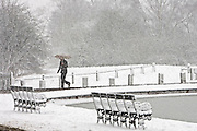 Man walks with umbrella across snow-covered Hampstead Heath, North London, United Kingdom