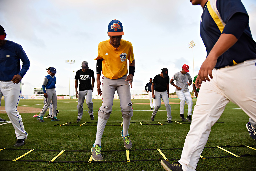 WILLEMSTAD, CURACAO - DECEMBER 11, 2014: Some of Curacao's best senior league players are put through drills for development at the Dutch Caribbean Baseball Academy in Santa Rosa to make them more viable for American college baseball programs as well as the major leagues. Catcher Quint Reinilla, 15, center (yellow) works on his footwork. (photo by Melissa Lyttle)