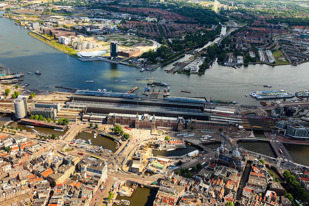 Nederland, Noord-Holland, Amsterdam, 14-06-2012; .Oosterdokseiland (ODE ). Zicht noord-oostwaarts op Amsterdam CS met IJ en Amsterdam-Noord(top). Links langs de IJ-oever het nieuwe filmmuseum Eye (wit gebouw) en de nieuwe stadsontwikkeling Overhoeks in Noord (voormalig Shell). Onder in beeld het stationsplein, trams, bussen, het nieuwe busstation,  rondvaartboten en ander verkeer. Rechts beneden de NIcolaaskerk aan de Prins Hendrikkade..View on Amsterdam Central Station in northern direction with IJ (river) and Amsterdam North (top). Top picture the newly constructed film museum Eye (white building) and the new urban residential development Overhoeks (former Shell). Bottom picture the station, trams, buses, new bus station, tour boats and other traffic. Right below the Nicholas Church on the Prins Hendrikkade. .luchtfoto (toeslag), aerial photo (additional fee required).foto/photo Siebe Swart