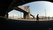 Pedestrian traffic in the shadow of the elevated FDR Highway in lower Manhattan, NY on Tuesday, June 1, 2004. The Brooklyn and Manhattan Bridges are seen in the background, which span the East River and connect lower Manhattan to Brooklyn.