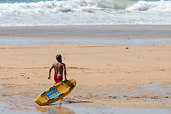 © Licensed to London News Pictures. 31/05/2020. Padstow, UK. A RNLI Lifeguard prepares to enter the water on Constantine beach on the north coast of Cornwall this afternoon. Yesterday the RNLI reinstated their beach lifeguard service, having not provided the usual lifeguard service for this time of year in Cornwall, due to Coronavirus (COVID-19). Photo credit : Tom Nicholson/LNP