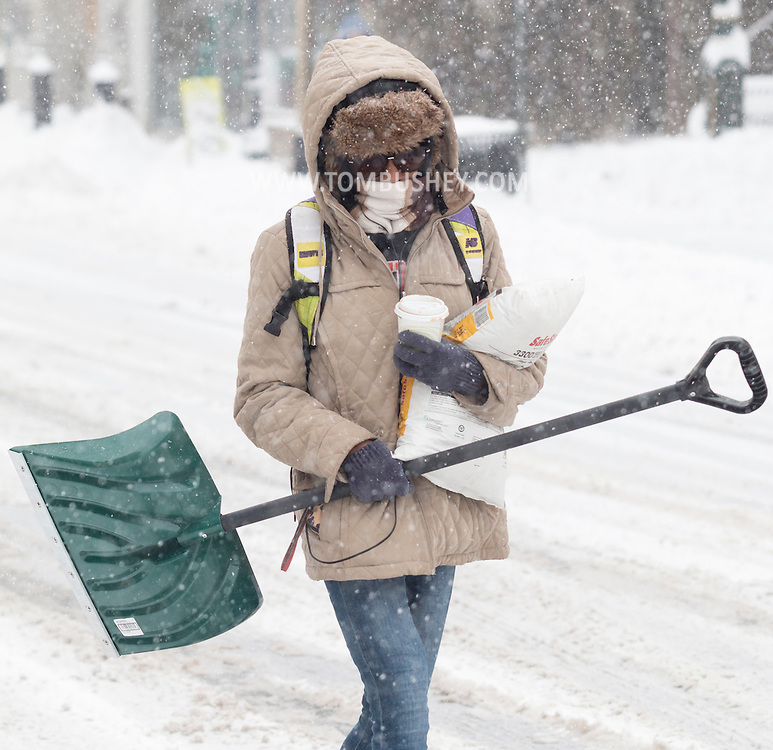 Middletown, New York - A woman caries a snow shovel on North Street during a snowstorm on Feb. 9, 2017.