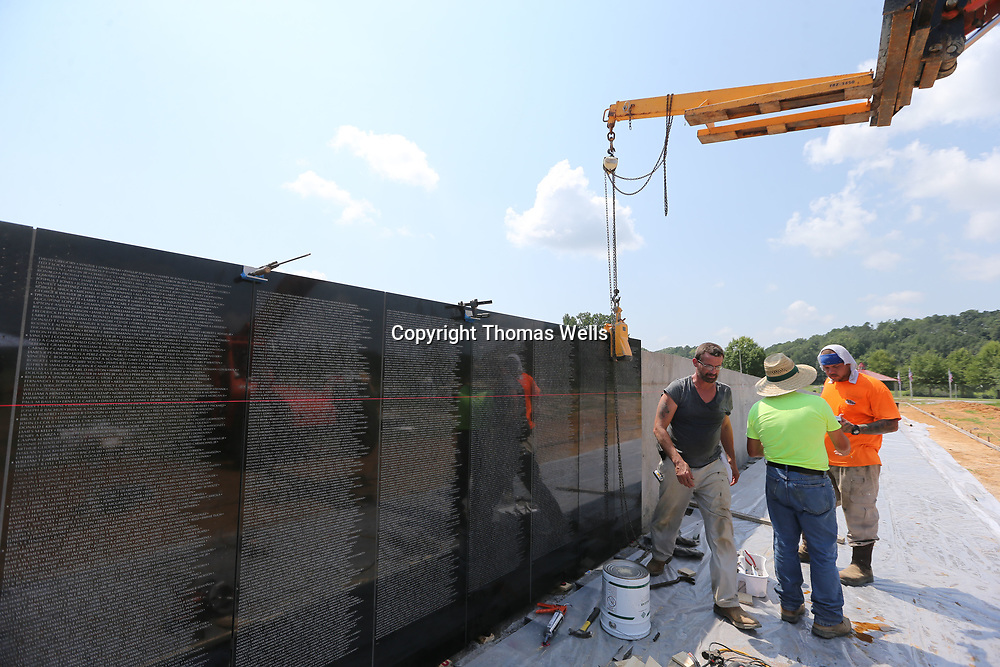 Roger Cole, from left, Rob Coulon and Phillip Taylor from Intrepid Stone and Marble of Harvey Louisiana begin installing the first sections of the new Vietenam Wall Memorial at Veterans Park on Wednesday.
