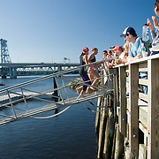 Two female triathletes run up a gangplank after completing their swim down the Kennebec river.  2007 Shipbuilders Triathlon in Bath, Maine.