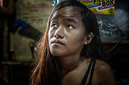 """Jasmin Dorana, 15, looks in a worried manner up at her mother-in-law as she discusses the execution of her son, John """"Toto"""" Dela Cruz, the father if Jasmin's baby daughter, Hazel, in the main room of the Dela Cruz' makeshift home built on posts above the waters of a contaminated estuary in Bagung Bayan, C4, Navotas.  Metro Manila, Philippines"""