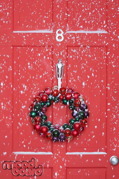 Christmas wreath hanging on door with snowfall