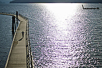 As the sun glimmers off the water of Lake Coeur d'Alene, a man walk along the ice free and dry floating boardwalk during an outing Monday.