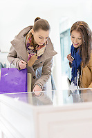 Young female friends looking at display cabinet in store