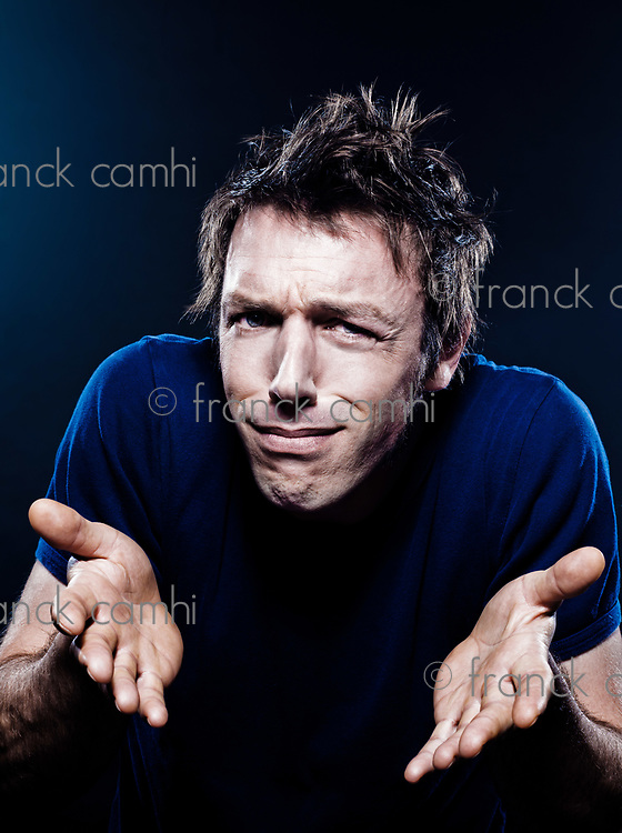 studio portrait on black background of a funny expressive caucasian man frowning anxious