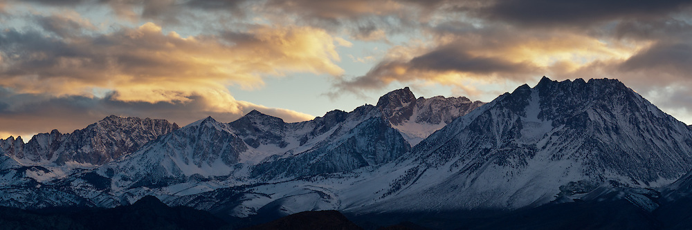 The sun lights stormy clounds as sets behind the eastern Sierra range, north of Bishop