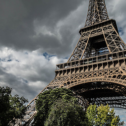 Eiffel tour in front of dramatic sky.