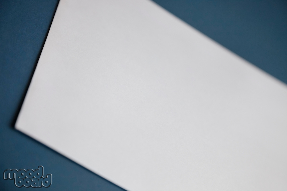 Cropped image of a blank white paper on dark blue surface