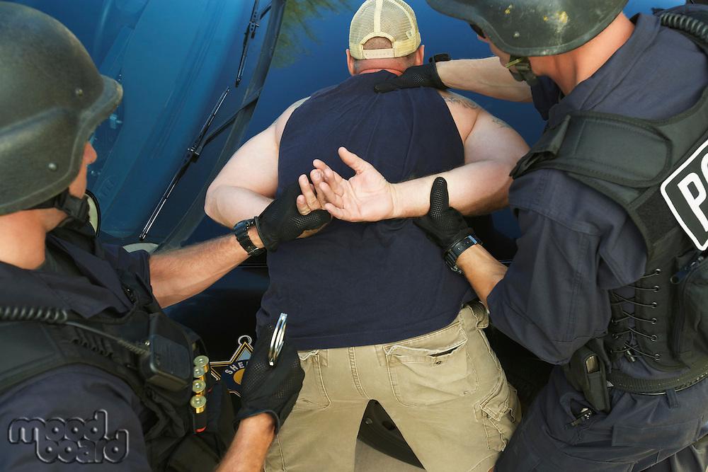 Police man putting handcuffs on criminal
