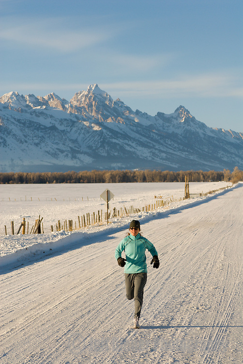 A young woman runs along a country road in Jackson Hole, Wyoming.
