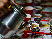 """05 SEPTEMBER 2017 - BANGKOK, THAILAND: A woman pours tea for ghosts at a Hungry Ghost banquet in Bangkok's Chinatown. The Ghost Festival is a Buddhist and Taoist holy day celebrated on the 15th day of the 7th lunar month. It is primarily celebrated in China and Chinese communities outisde China. In Thailand, it's celebrated in Thai-Chinese communities in Bangkok, Phuket and Chiang Mai.  On that day ghosts and spirits, including those of the deceased ancestors, come out from the lower realm to visit the living. Families prepare elaborate banquets for the spirits and burn """"ghost money"""" for the spirits to use in the other realm. It is a day for venerating dead relatives.      PHOTO BY JACK KURTZ"""