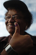 Presidential candidate Ellen Johnson Sirleaf shows off the purple dye on her thumb after casting her ballot in her hometown of Tubmanburg.