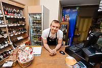 Portrait of salesman leaning at cash counter in supermarket