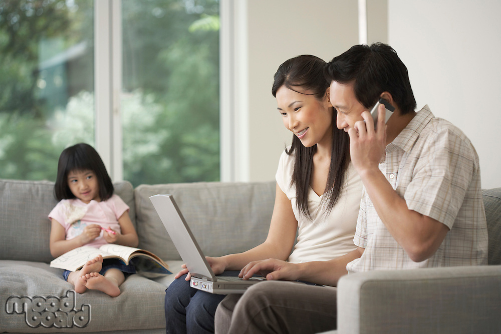 Asian couple using laptop on sofa with daughter watching in background