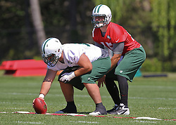 Jun 7, 2012; Florham Park, NJ, USA; New York Jets quarterback Tim Tebow (15) takes a snap from New York Jets guard Caleb Schlauderaff (72) during the New York Jets organized team activities at the Atlantic Health Training Center.